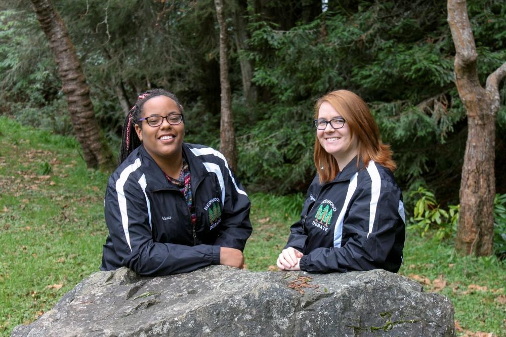 HSU debate team alumni posing in their debate team jackets leaning on a bolder.