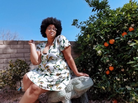 Sabina Gallier sitting next to a citrus tree wearing a dress.